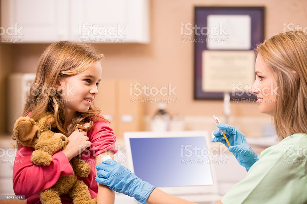 Female nurse or doctor gives vaccine to girl patient. Office. stock photo