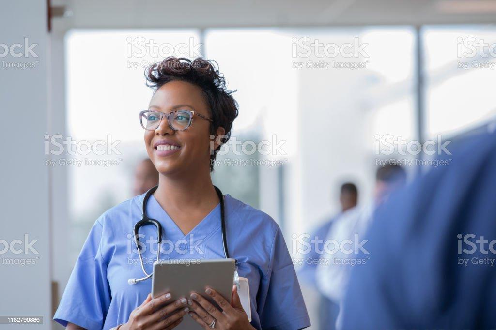 Kvinnlig sjuksköterska eller läkare ler medan stirrade ut fönster i sjukhus hallen och hålla Digital tablett med elektronisk patientfil - Royaltyfri Afrikanskt ursprung Bildbanksbilder