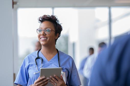 Kvinnlig Sjuksköterska Eller Läkare Ler Medan Stirrade Ut Fönster I Sjukhus Hallen Och Hålla Digital Tablett Med Elektronisk Patientfil-foton och fler bilder på Afrikanskt ursprung