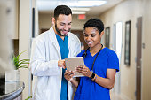 istock Female nurse showing doctor digital tablet with medical results 1201050310
