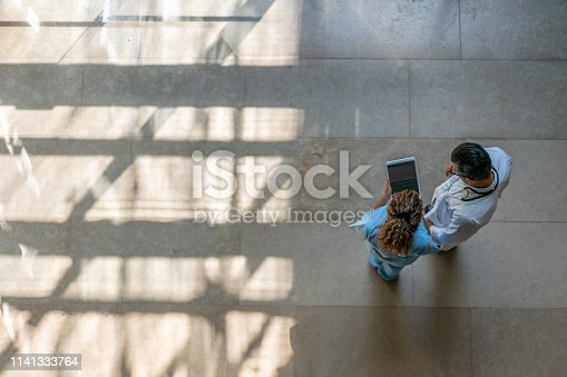 Female nurse showing something to doctor on tablet at the hospital - High angle view