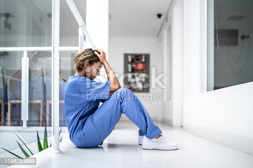 Female nurse sitting on the floor and looking distraught