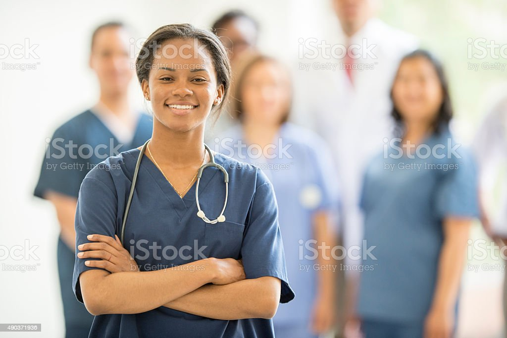 Female Nurse Standing and Smiling with Associates stock photo