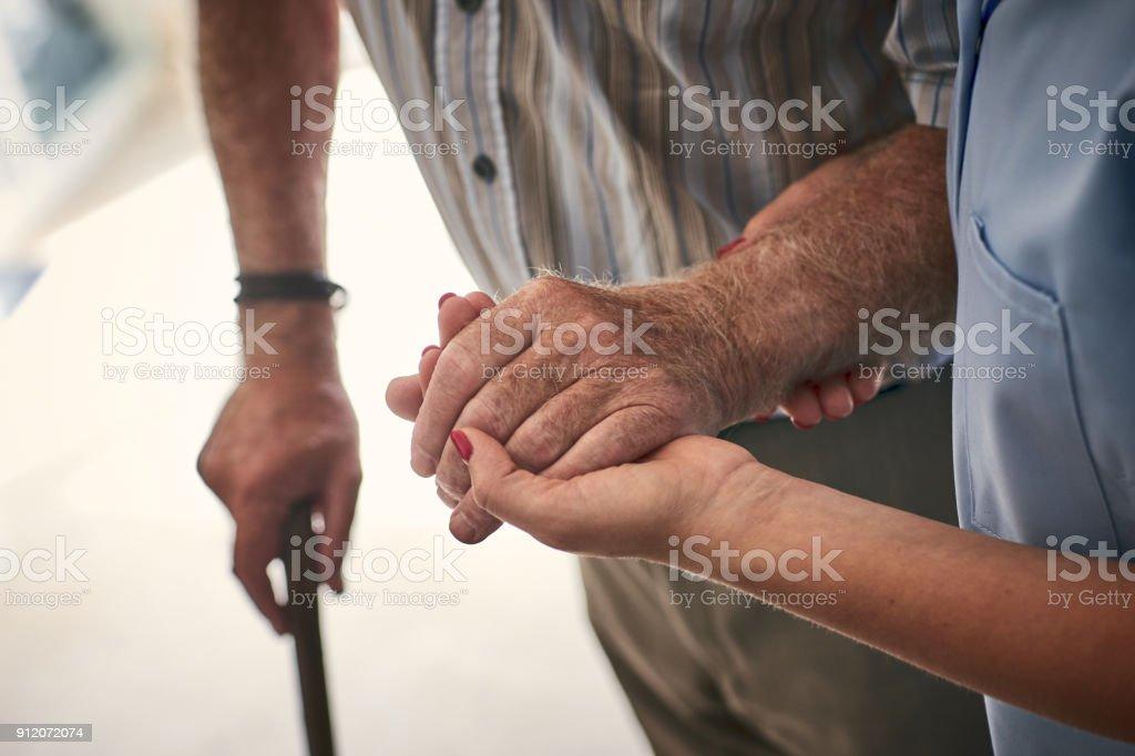 Female nurse supporting senior man to walk stock photo