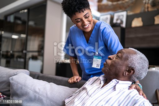 Female nurse taking care of a senior man at home