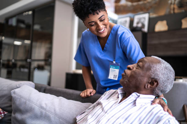 Female nurse taking care of a senior man at home Female nurse taking care of a senior man at home well structure stock pictures, royalty-free photos & images