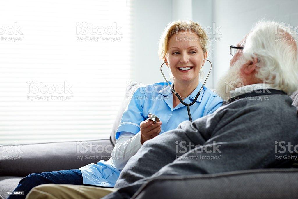 Female nurse taking care of senior man at home stock photo