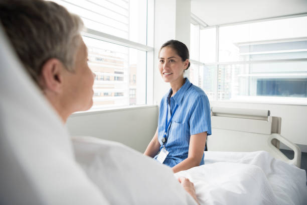female nurse talking and smiling with woman recovering in hospital ward - australian nurses stock photos and pictures