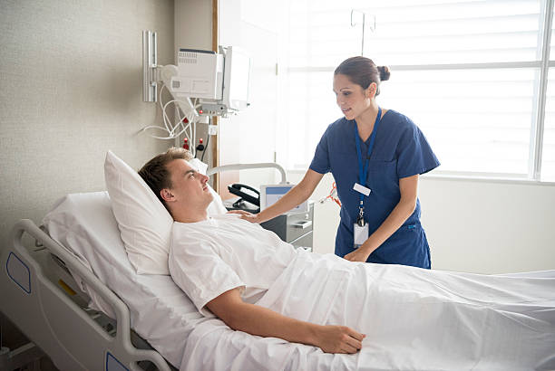female nurse tending to male patient in hospital bed - australian nurses stock photos and pictures