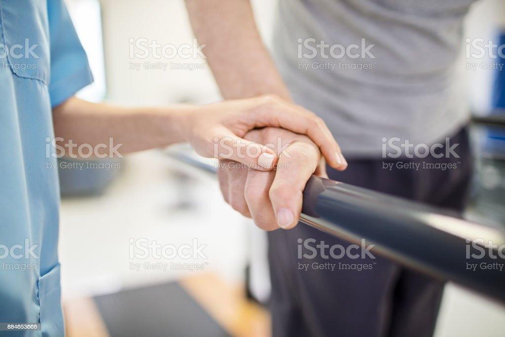 Female nurse touching senior man's hand on railing royalty-free stock photo