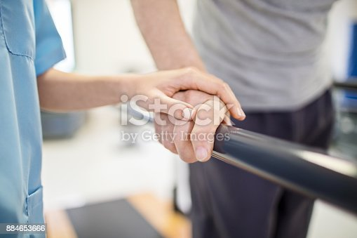 Cropped image of female nurse touching senior man's hand on railing. Medical professional is assisting senior man to walk. Elderly patient is walking between parallel bars in rehabilitation center.