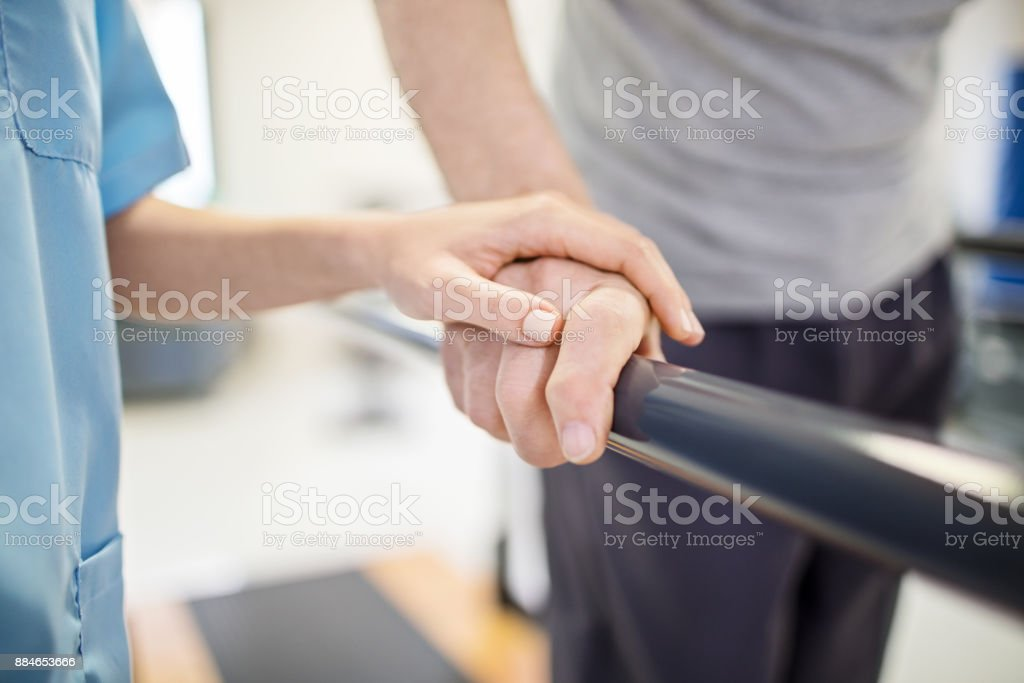 Female nurse touching senior man's hand on railing stock photo