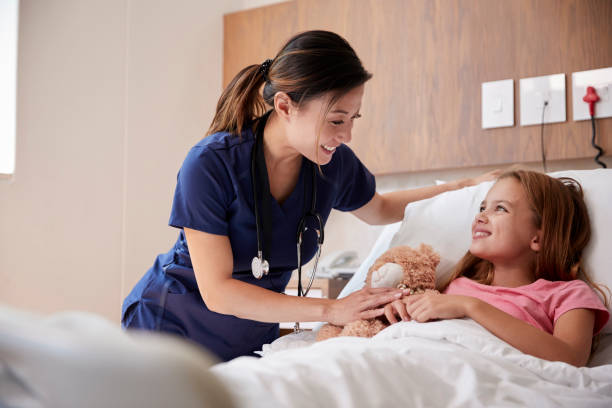 Female Nurse Visiting Girl Lying In Hospital Bed Hugging Teddy Bear Female Nurse Visiting Girl Lying In Hospital Bed Hugging Teddy Bear nurses stock pictures, royalty-free photos & images