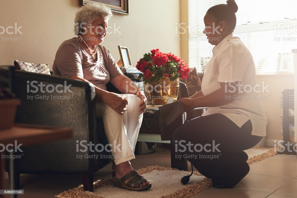 Female nurse visiting senior patient for checking blood pressure stock photo