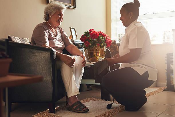 female nurse visiting senior patient for checking blood pressure - infermiera personale medico foto e immagini stock