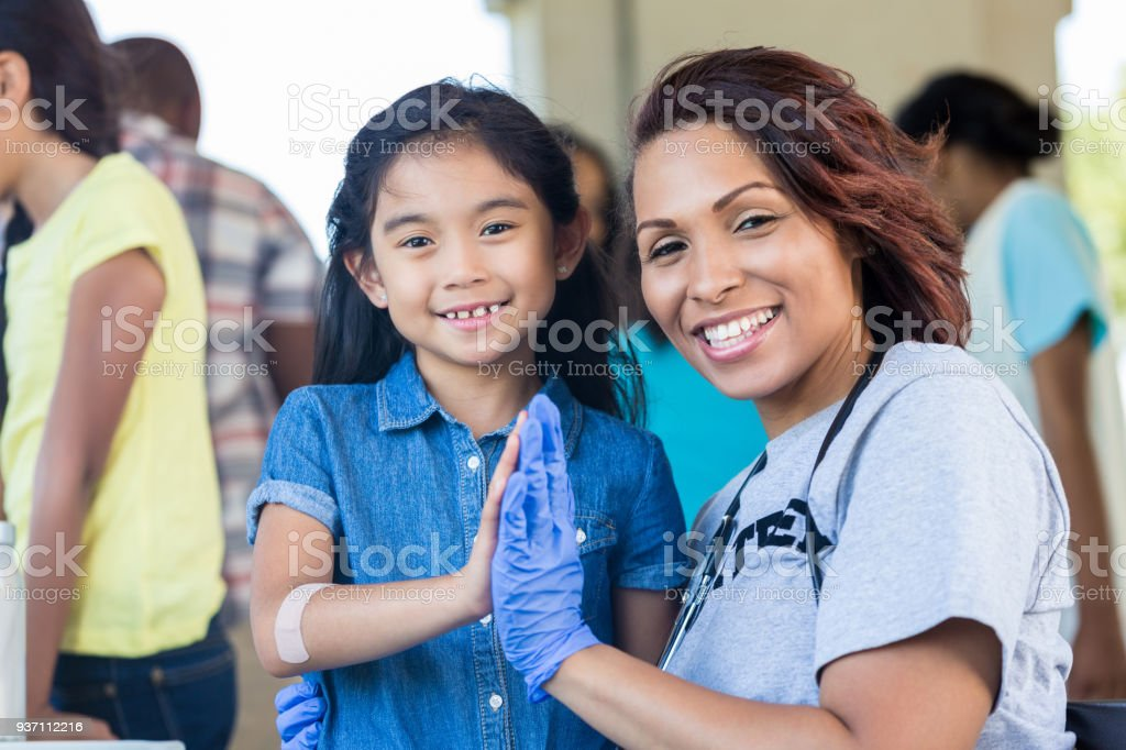 Female nurse volunteering at health fair stock photo