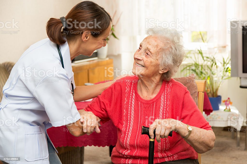 Female nurse with senior woman patient stock photo
