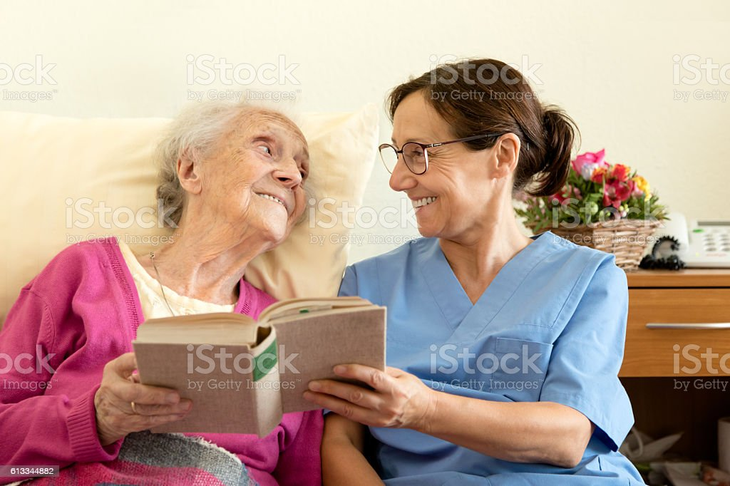 Female nurse with senior woman patient, reading a book stock photo