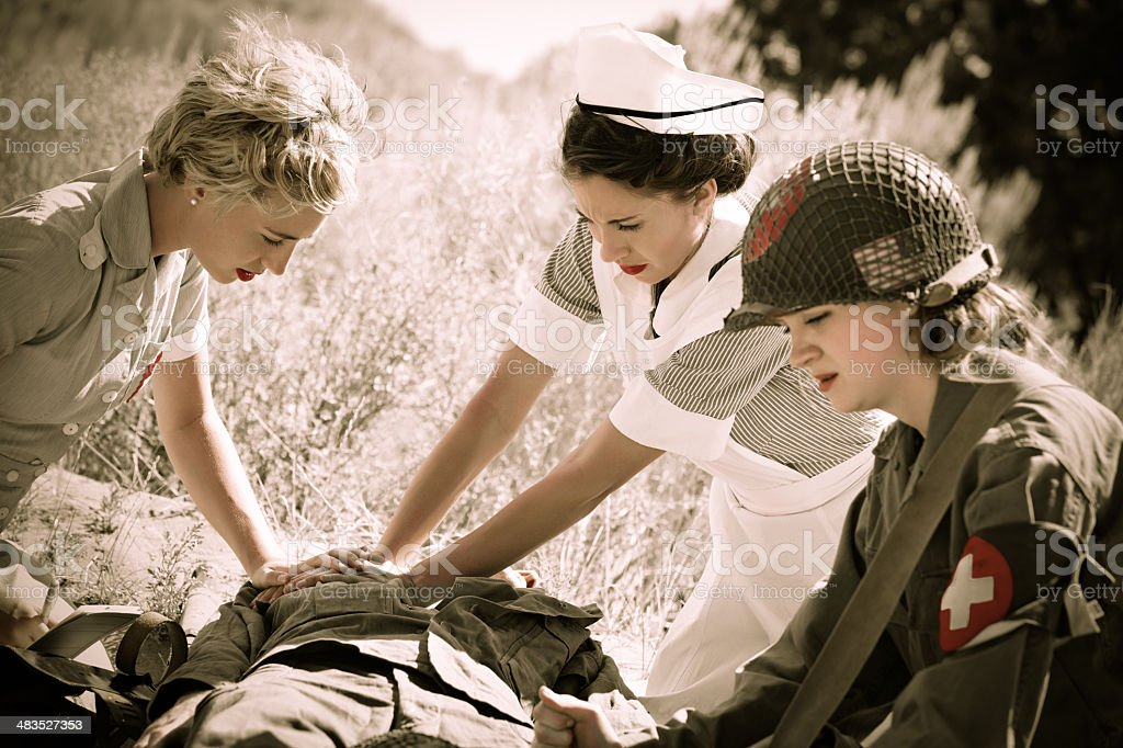 Female nurses & medic assisting wounded soldier in field stock photo