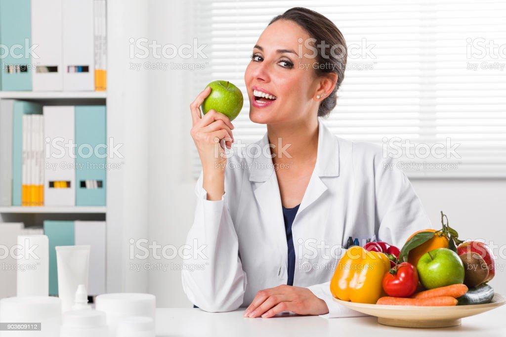 Weibliche Ernährungsberaterin in ihrem Büro einen grünen Apfel zu essen – Foto
