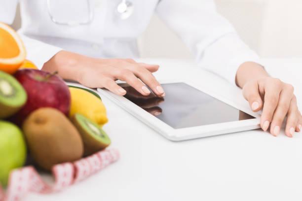 weibliche ernährungsberaterin hände auf digitale tablet im büro arbeiten - menüplanung vorlagen stock-fotos und bilder