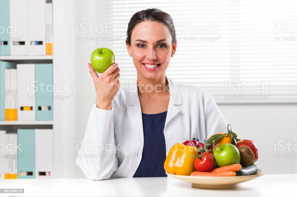 Female nutritionist holding a green apple – Foto