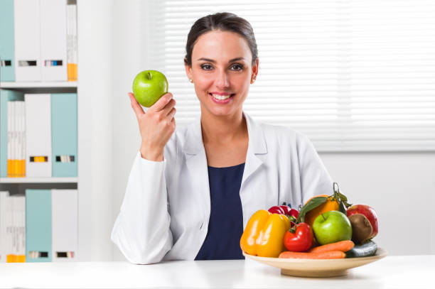 Female nutritionist holding a green apple stock photo
