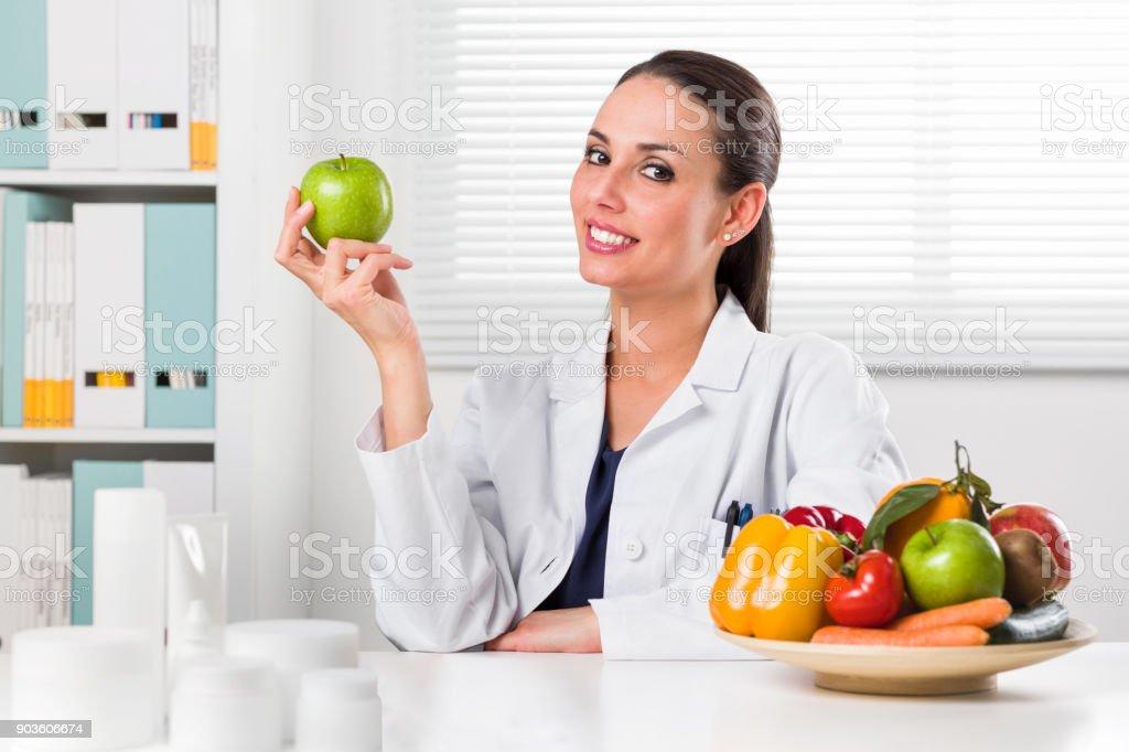 Weibliche Ernährungsberaterin hält einen grünen Apfel – Foto