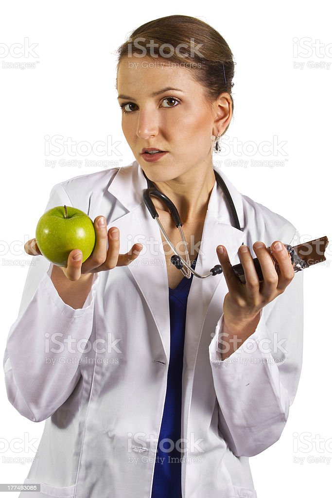Female Nutritionist Holding an Apple and a Chocolate Bar royalty-free stock photo