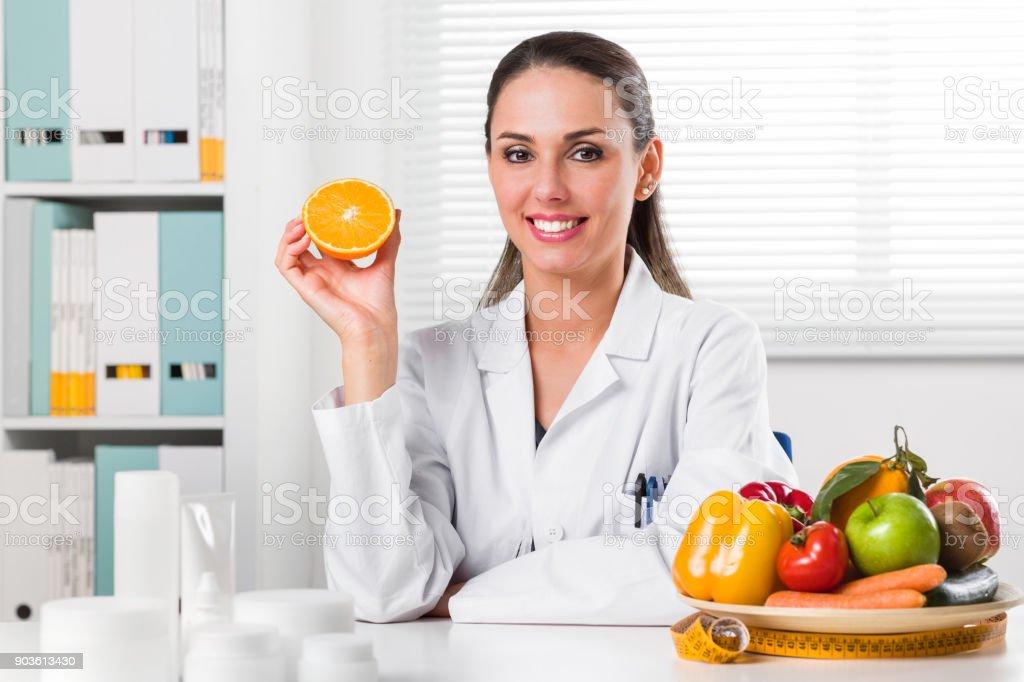 Weibliche Ernährungsberater mit einer Orangenscheibe – Foto