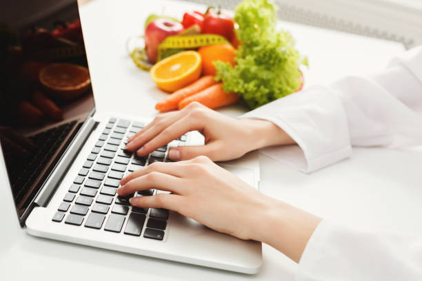 female nutritionist working on laptop - dietician stock pictures, royalty-free photos & images
