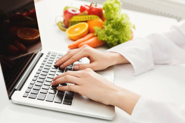 weibliche ernährungsberaterin arbeiten am laptop - menüplanung vorlagen stock-fotos und bilder