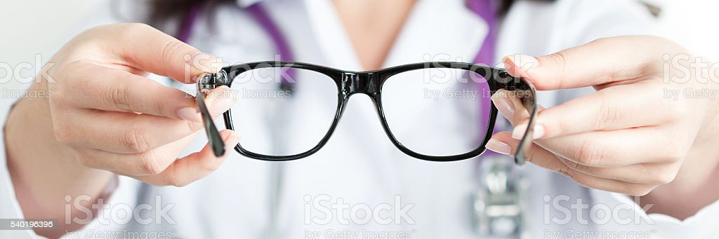 Female oculist doctor's hands giving a pair of black glasses stock photo