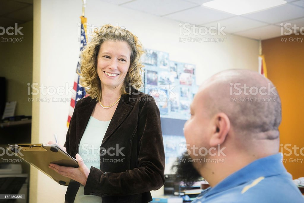 Female Office Receptionist Registering Client On Note Pad royalty-free stock photo