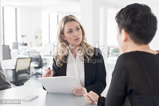 istock Female office worker discussing with colleague in modern office 519552854