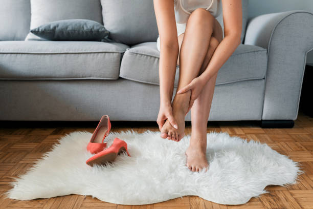female office worker finished work back to home sitting and relaxing and feeling feet painful take off high heel shoes using hand massage - human foot stock photos and pictures