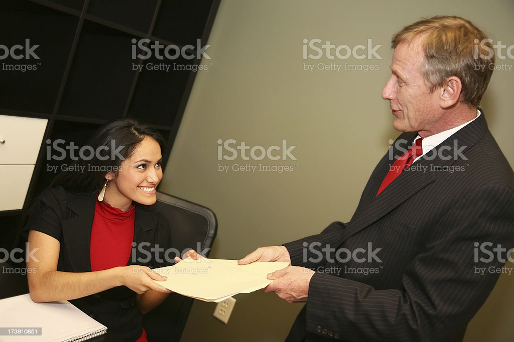 Female Office Worker Happily Receiving a File from Co-Worker royalty-free stock photo