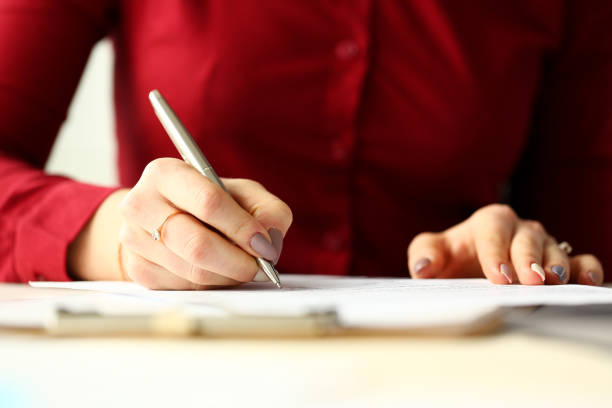 Female office worker holding silver pen filling out some application form stock photo