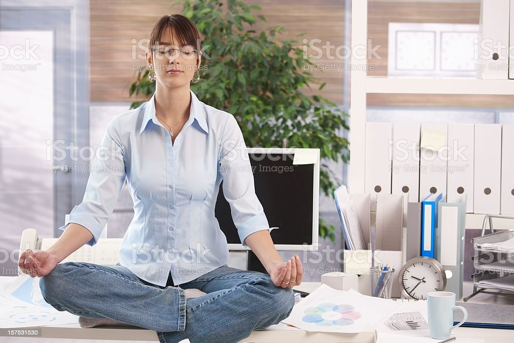 Female office worker meditating on her desk royalty-free stock photo