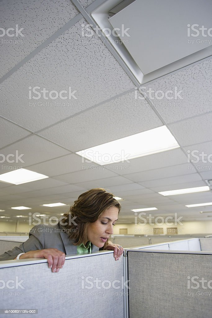 Female office worker peering over partition into office cubicle Lizenzfreies stock-foto