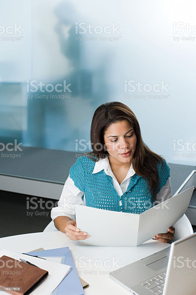 Female office worker reading a document 免版稅 stock photo