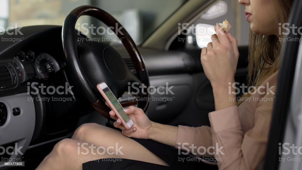 Female office worker sitting in car, eating sandwich and using...
