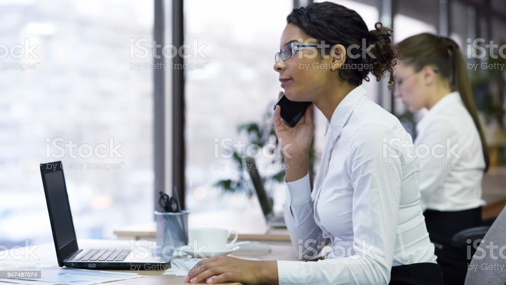 Female office worker talks on smartphone with client, accepts customer orders stock photo