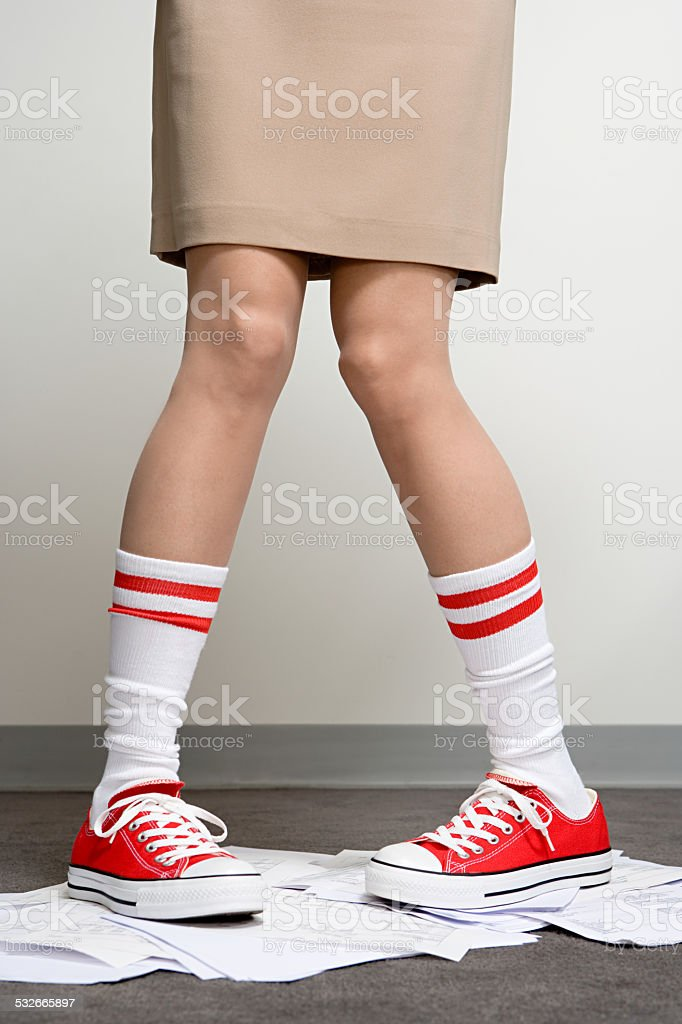 Female office worker wearing baseball boots stock photo