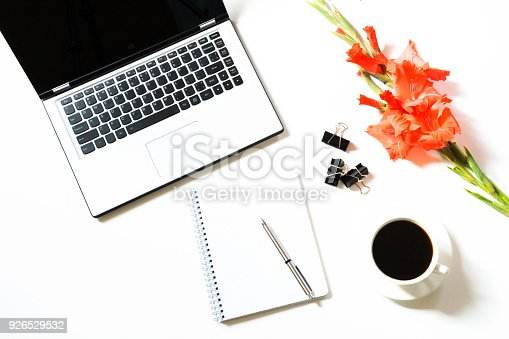 istock Female office workplace with laptop, cup of coffee, accessories, gladiolus flower on white. Business concept. Top view with copy space. 926529532