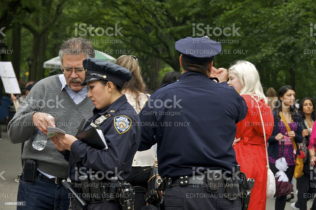 NYPD Female officer helps person with directions, Central Park, NYC stock photo