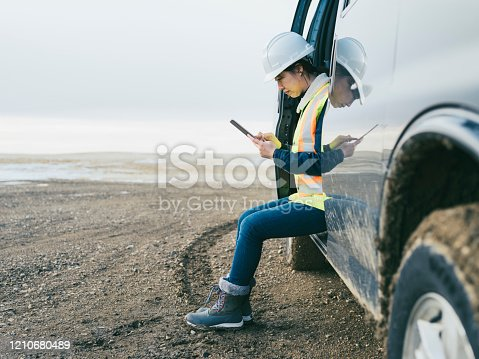 istock female oil Worker using  tablet pc 1210680489