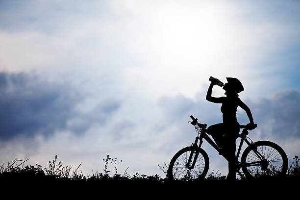 """Female on a bicycle refreshing """"Young female on a bicycle holding bottle of drink, silhouette in the natureplease visit my portfolio for other pictures.more silhouettes:"""" female biker resting stock pictures, royalty-free photos & images"""