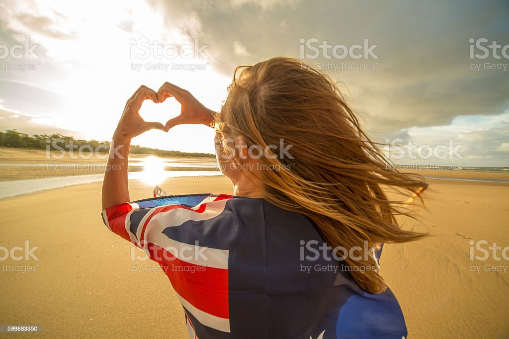Female on beach makes heart shape finger frame, Australian flag stock photo