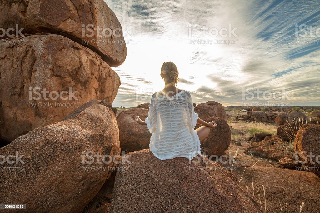 Female on boulder exercises yoga at sunset stock photo